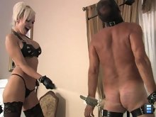 When he cries out in pain she shoves a riding crop in his mouth and tells him that his balls are next!