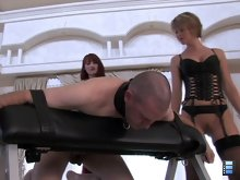 Kendra and Brianna have their slut bend over, strapped down and his ass perfectly exposed.